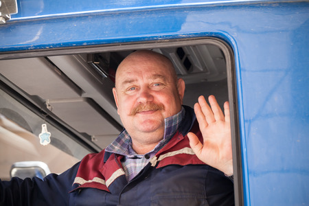 trucker: Saint-Petersburg, Russia - May 30, 2015: Senior mustached truck driver smiles and says hello from his blue lorry cabin Editorial