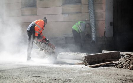 stone cutter: Saint-Petersburg, Russia - May 23, 2015: men at work, urban road under construction, sawing of roadside border stones