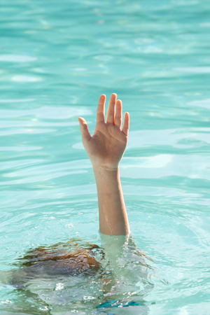 Hand of a drowning person stretching out of sea water pool and asking for help