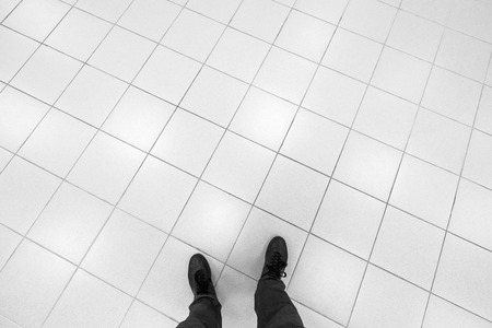 Mannelijke voeten staan op kantoor vloer met witte glanzende vierkante tegels Stockfoto