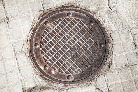 the hatch: Round rusted hatch in urban pavement, sewer manhole cover