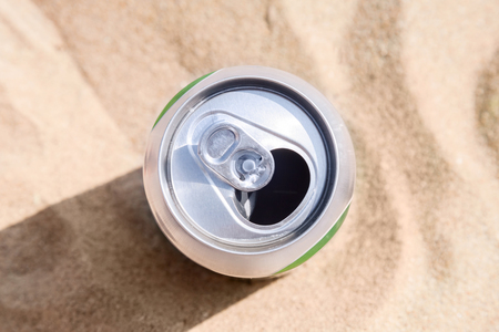 Aluminum can of beer stands on a beach sand