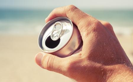 bebidas frias: Aluminio lata de cerveza en la mano masculina con la playa y el mar borrosa sobre un fondo