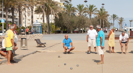 spaniards: Calafell, Spain - August 20, 2014: Seniors Spaniards play Bocce on sandy beach in Calafell, resort town in Catalonia