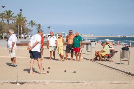 spaniards: Calafell, Spain - August 20, 2014: Seniors Spaniards play Bocce on a sandy beach in Calafell, resort town in Catalonia