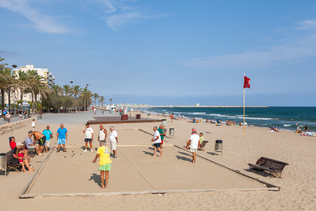 Calafell, Spain - August 20, 2014: Seniors Spaniards play Bocce on a sandy beach in Calafell, small resort town in Catalonia