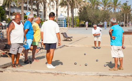 spaniards: Calafell, Spain - August 20, 2014: Seniors Spaniards play Bocce on sandy beach in Calafell, small resort town in Catalonia