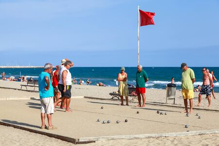 spaniards: Calafell, Spain - August 20, 2014: Seniors Spaniards play Bocce on a sandy beach in Calafell, small resort town in Catalonia