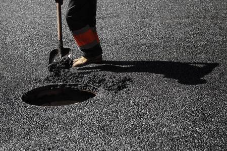 asphalting: Urban road under construction, asphalting in progress, worker with a shovel near sewer manhole
