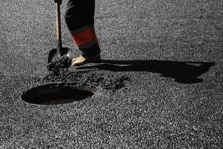 asphalting: Urban road under construction, asphalting in progress, worker with a shovel near sewer manhole