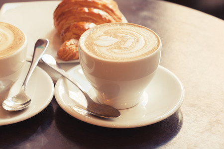coffee foam: Cappuccino with croissant. Stock Photo
