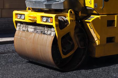 asphalting: Urban road is under construction, asphalting in progress, fragment of yellow roller