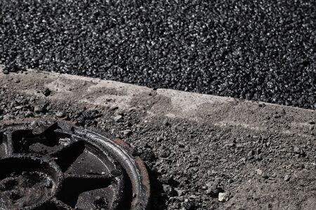 asphalting: Urban road under construction, asphalting in progress. Dirty sewer manhole cover lays on a roadside Stock Photo