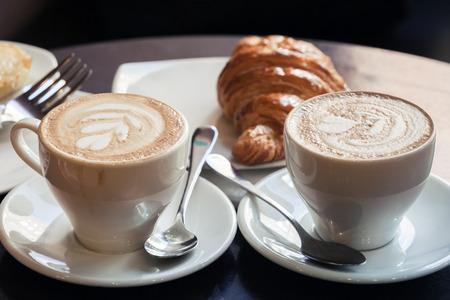 クロワッサンとカプチーノ。カフェテリア、ビンテージの色調補正写真フィルター、古いスタイルの効果で表に 2 杯のコーヒーとミルクの泡が立っ