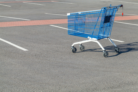 Empty shopping cart stands on a parking near supermarket 版權商用圖片