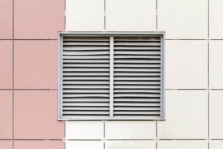 Gray ventilation grille on the window, modern industrial building facade fragment photo