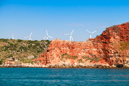 headland: Kaliakra headland. Bulgaria, Black Sea. Coastal landscape with red cliff and wind turbines