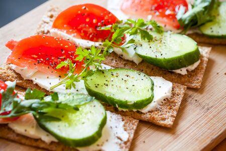 comiendo pan: Tema de la comida sana. Sandwiches. Pan finland�s centeno crujiente, queso fresco, pepino, tomate, perejil y pimienta negro Foto de archivo