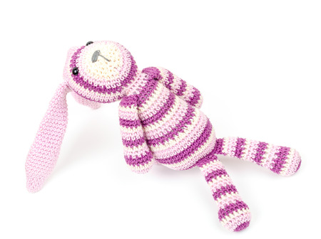 Knitted rabbit toy is sitting and looks up, photo isolated on white background photo