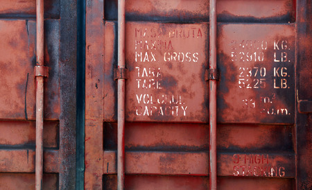 Old red shipping container door with technical characteristics text, background photo texture
