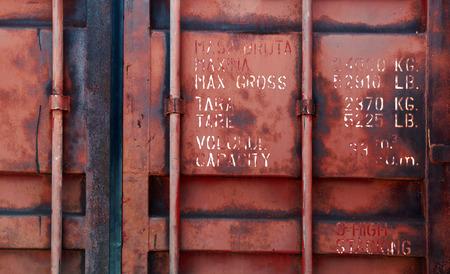 Oude rode container deur met technische kenmerken tekst, achtergrond fototextuur Stockfoto