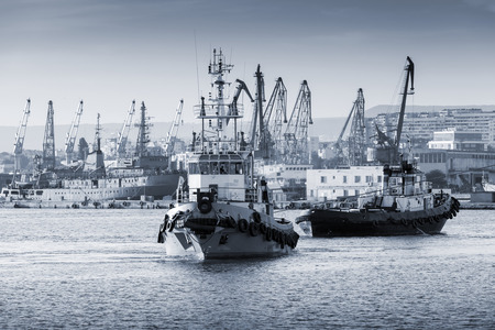 tonal: Tug boats are working in Varna harbor. Black Sea, Bulgaria. Vintage stylized photo with monochrome blue tonal photo filter
