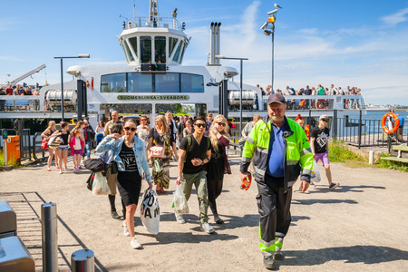 descend: Helsinki, Finland - June 13, 2015: Tourists descend from the Suomenlinna II ship to the pier. This ferry travels from Helsinki to Suomenlinna island and back Editorial