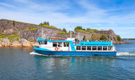 ms: Helsinki, Finland - June 13, 2015: Small passenger ship MS Amiraali operated by JT-Line enters the harbor of Suomenlinna island. Tourists sit on the upper deck and in lounge