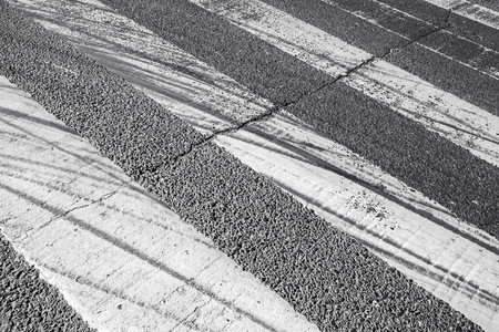 tire tracks: Tire tracks over pedestrian crossing road marking on dark asphalt