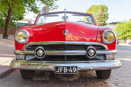 front view: Helsinki, Finland - June 13, 2015: Old red Ford Custom Deluxe Tudor car is parked on the roadside. 1951 year modification with convertible roof, closeup front view Editorial