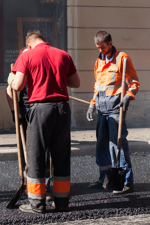 asphalting: Saint-Petersburg, Russia - May 30, 2015: men at work, urban road is under construction, asphalting in progress group workers stand with shovels