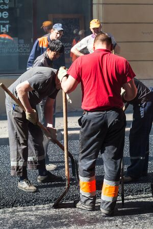 asphalting: Saint-Petersburg, Russia - May 30, 2015: men at work, urban road is under construction, asphalting in progress group workers with shovels
