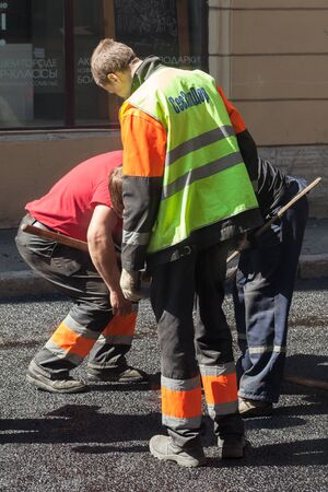 asphalting: Saint-Petersburg, Russia - May 30, 2015: men at work, urban road under construction, asphalting in progress group workers with shovels Editorial