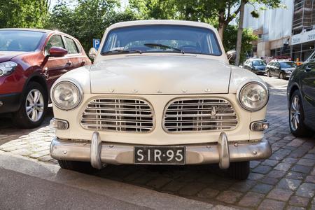 roadside stand: Helsinki, Finland - June 13, 2015: Old white Volvo Amazon 121 B12 car is parked on the roadside in Helsinki city. Front view