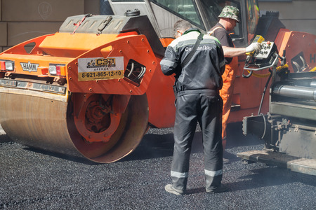 asphalting: Saint-Petersburg, Russia - May 30, 2015: men at work, urban road is under construction, asphalting in progress, quality control manager works near the paver operator Editorial