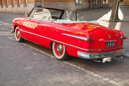 tudor: Helsinki, Finland - June 13, 2015: Old red Ford Custom Deluxe Tudor car is parked on the roadside. 1951 year modification with convertible roof, back view