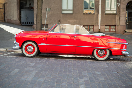 tudor: Helsinki, Finland - June 13, 2015: Old red Ford Custom Deluxe Tudor car is parked on the roadside. 1951 year modification with convertible roof, side view