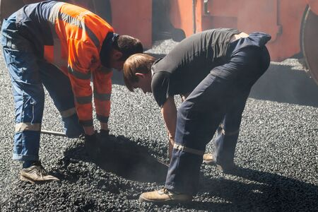 asphalting: Saint-Petersburg, Russia - May 30, 2015: men at work, urban road under construction, asphalting in progress, two workers install sewer manhole