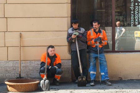 asphalting: Saint-Petersburg, Russia - May 30, 2015: men at work, urban road under construction, asphalting, group workers with shovels