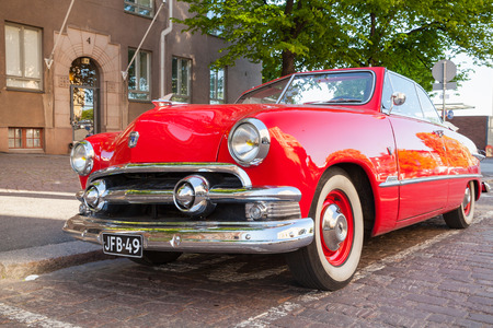 tudor: Helsinki, Finland - June 13, 2015: Old red Ford Custom Deluxe Tudor car is parked on the roadside. 1951 year modification with convertible roof, closeup photo