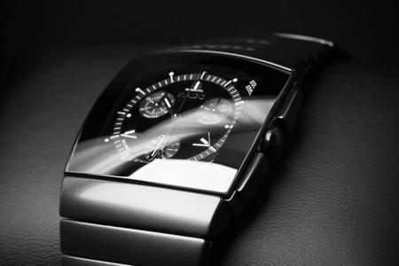 cronografo: San Petersburgo, Rusia - 18 de junio 2015: Rado Sintra Chrono pone en cuero de telón de fondo, para hombre reloj cronógrafo hecha de cerámica de alta tecnología negro. Primer foto de estudio con enfoque selectivo