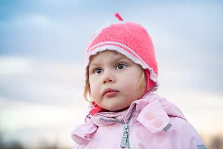 pink hat: Cute Caucasian blond baby girl in pink hat, outdoor closeup portrait