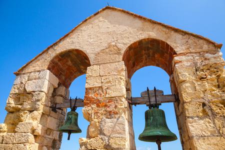 arcos de piedra: Castillo de piedra medieval en la ciudad de Calafell, Espa�a. Dos campanas que cuelgan en arcos sobre fondo de cielo azul