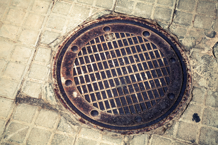 tonal: Round rusted hatch in urban pavement, sewer manhole cover, vintage tonal correction old style filter effect