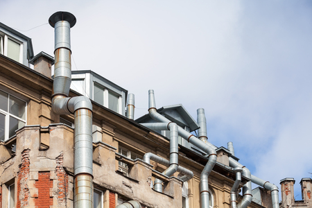 roofing system: New attic windows in old living house roof with ventilation pipes, high-tech architecture Stock Photo
