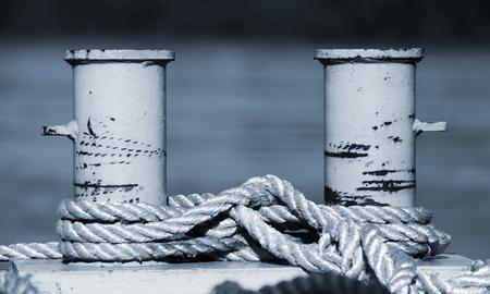 cleat: Big mooring bollard with nautical ropes, blue toned monochrome photo