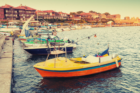 Small wooden boats in Nesebar, ancient historical town, Black Sea coast, Bulgaria. Vintage retro stylized photo with tonal correction filter, instagram style Stock Photo