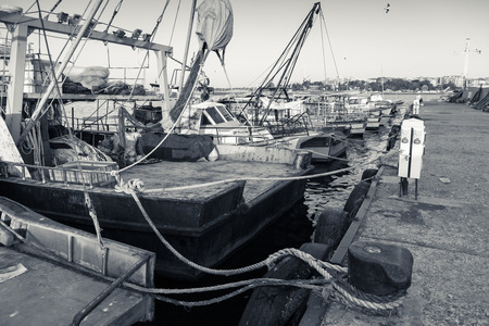 commercial fishing net: Moored fishing boats with drying nets in Nesebar town, Bulgaria. Vintage stylized monochrome photo Stock Photo
