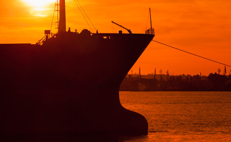 ship bow: Big industrial cargo ship bow silhouette in bright orange sunset sun light, Varna harbor, Bulgaria. Photo with natural lens flare effect