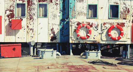 superstructure: Old industrial ship rusted white superstructure wall with lifebuoys. Vintage retro stylized photo with tonal correction filter, instagram style